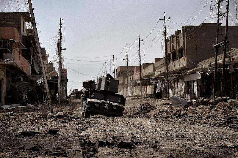 Iraqi special forces drive through a heavily damaged street in Mosul, on March 1, 2017 (AFP Photo/ARIS MESSINIS)