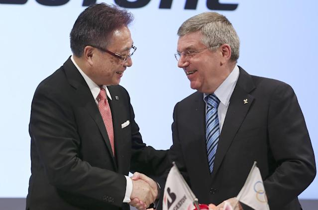International Olympic Committee (IOC) President Thomas Bach, right, and Bridgestone Corp. CEO Masaaki Tsuya shakes hands during a press conference in Tokyo, Friday, June 13, 2014. Japanese tire manufacturer Bridgestone signed an agreement on Friday to become a top-tier sponsor of the IOC in a 10-year deal that will cover the 2020 Tokyo Games. Bridgestone officials declined to reveal financial terms of the deal but the Asahi Shimbun newspaper reported that Bridgestone will pay $344 million to become a worldwide sponsor under the IOC's global commercial program, known as TOP. (AP Photo/Koji Sasahara)