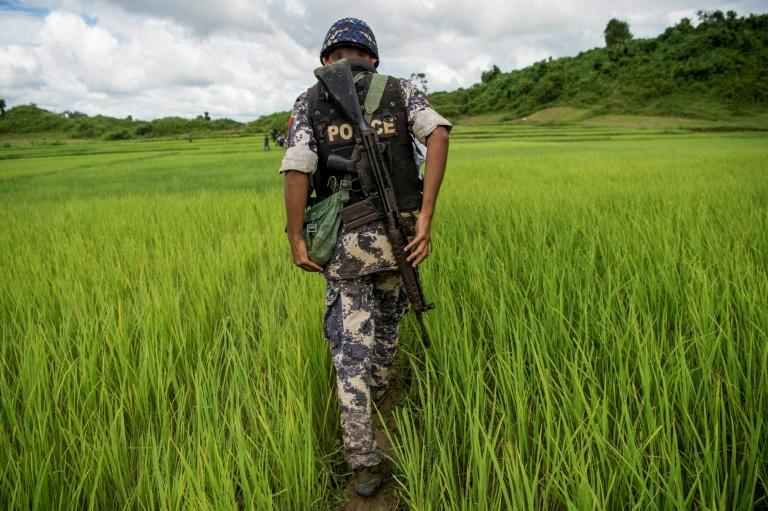 A Myanmar border guard walks near a mass grave discovered in violence-wracked Rakhine state in September 2017