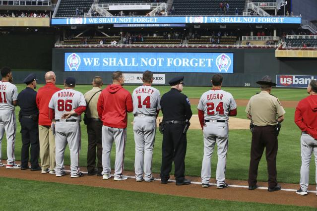Washington Nationals players join first responders during the national anthem as the 18th anniversary of the attacks on Sept. 11, 2001, was observed, before the team's baseball game against the Minnesota Twins on Wednesday, Sept. 11, 2019, in Minneapolis. (AP Photo/Jim Mone)