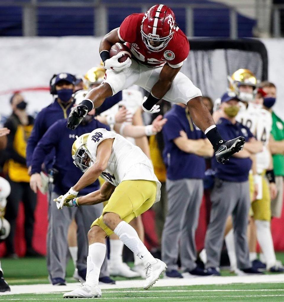 Alabama running back Najee Harris (22) leaps over Notre Dame cornerback Nick McCloud (4) as he makes a long run Jan. 1, 2021, in the College Football Playoff semifinal hosted by the Rose Bowl in AT&T Stadium.