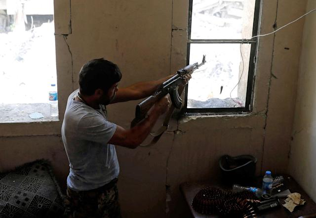 <p>A fighter of the Syrian Democratic Forces fires his weapon towards the positions of the Islamic State militants in the National Hospital, at the frontline in Raqqa, Syria, Oct. 8, 2017. (Photo: Erik De Castro/Reuters) </p>