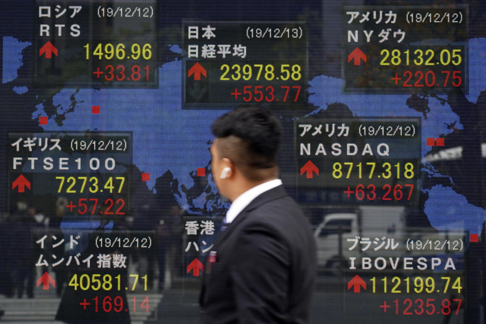 A man looks at an electronic stock board showing Japan's Nikkei 225 index and other country's index at a securities firm in Tokyo Friday, Dec. 13, 2019. Shares likewise jumped Friday in Asia following fresh all-time highs overnight on Wall Street spurred by optimism that the U.S. and China are close to reaching a deal to end their costly trade war. (AP Photo/Eugene Hoshiko)