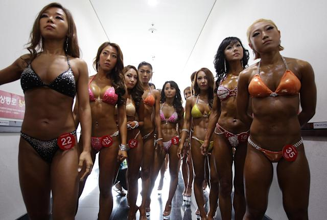 DAEGU, SOUTH KOREA - APRIL 13: Female bodybuilders prepare themselves for judging backstage during the 2014 NABBA/WFF Korea Championship on April 13, 2014 in Daegu, South Korea. (Photo by Chung Sung-Jun/Getty Images)
