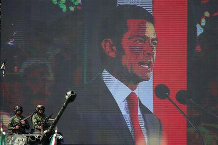 Soldiers are pictured as Mexico's President Enrique Pena Nieto is seen on giant screen during Flag Day celebrations at Campo Marte in Mexico City, Mexico February 24, 2018. REUTERS/Edgard Garrido