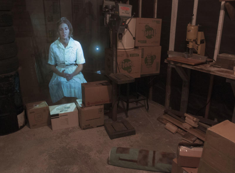 CORRECTS DATE OF MUSEUM OPENING TO NOV. 6 - In this Oct. 29, 2013 photo, an image of an actress portraying Marina Oswald, wife of Lee Harvey Oswald, is projected in the garage of the Ruth Paine House Museum, in Irving. The museum in the small, two-bedroom home that once belonged to Ruth Paine, who had befriended Marina and let her live there with her two daughters, will open Wednesday, Nov. 6, 2013. (AP Photo/Rex C. Curry)