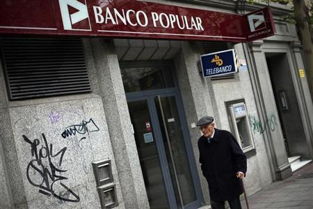 A man walks past a branch of Spanish Banco Popular bank in Madrid