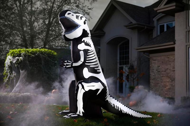 Dark front yard with a black and white inflatable that looks like a dinosaur