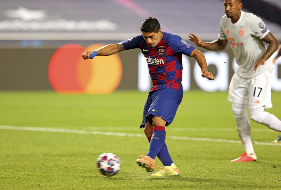 Barcelona's Luis Suarez, left, scores a goal during the Champions League quarterfinal soccer match between Barcelona and Bayern Munich in Lisbon, Portugal, Friday, Aug. 14, 2020. (Rafael Marchante/Pool via AP)