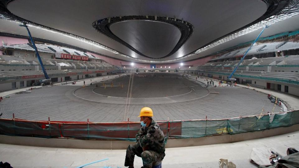 """A construction worker sits in the National Speed Skating Oval, known colloquially as the """"Ice Ribbon"""", which will host the 2021 World Speed Skating Championships and the speed skating competitions at the 2022 Winter Olympics in Beijing, China, September 23, 2020."""