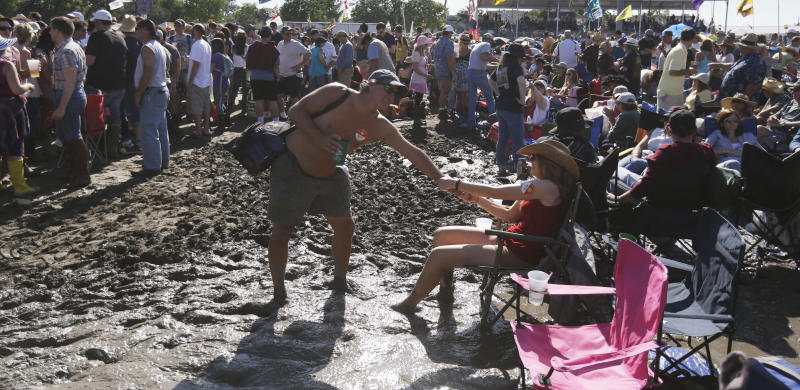 Festival-goers wait in mud, caused by recent rains, for Fleetwood Mac to perform at the New Orleans Jazz and Heritage Festival in New Orleans, Saturday, May 4, 2013. (AP Photo/Gerald Herbert)