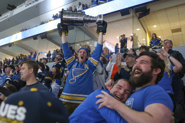 A St. Louis Blues fan at a hoists a replica Stanley Cup in celebration at a watch party in the Enterprise Center in St. Louis after the Blues scored a goal during the first period of Game 7 of the NHL hockey Stanley Cup Final against the Boston Bruins in Boston. (AP Photo/Scott Kane)