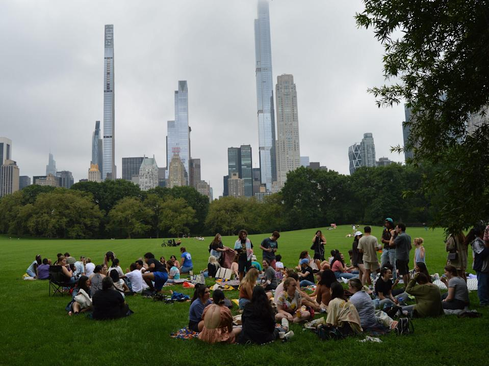 Dozens of people sit on the grass chatting in Central Park, with New York City skyscrapers behind them.