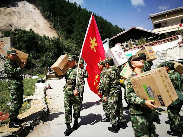 <p>Chinese paramilitary police carry relief supplies on their way to an earthquake-stricken zone in Jiuzhaigou in China's southwestern Sichuan province on Aug. 9, 2017. (Photo: STR/AFP/Getty Images) </p>
