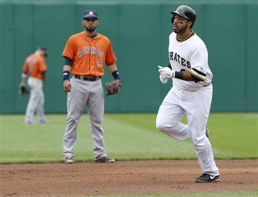 Pittsburgh Pirates' Pedro Alvarez, right, rounds the bases in front of Houston Astros shortstop Marwin Gonzalez (9) after hitting a home run in the fifth inning of the baseball game on Sunday, May 19, 2013, in Pittsburgh. (AP Photo/Keith Srakocic)