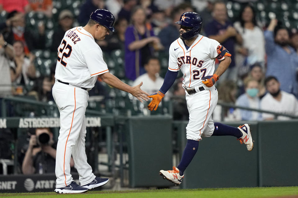 Houston Astros' Jose Altuve (27) is congratulated by first base coach Omar Lopez (22) after hitting a home run against the Los Angeles Angels during the first inning of a baseball game Wednesday, May 12, 2021, in Houston. (AP Photo/David J. Phillip)