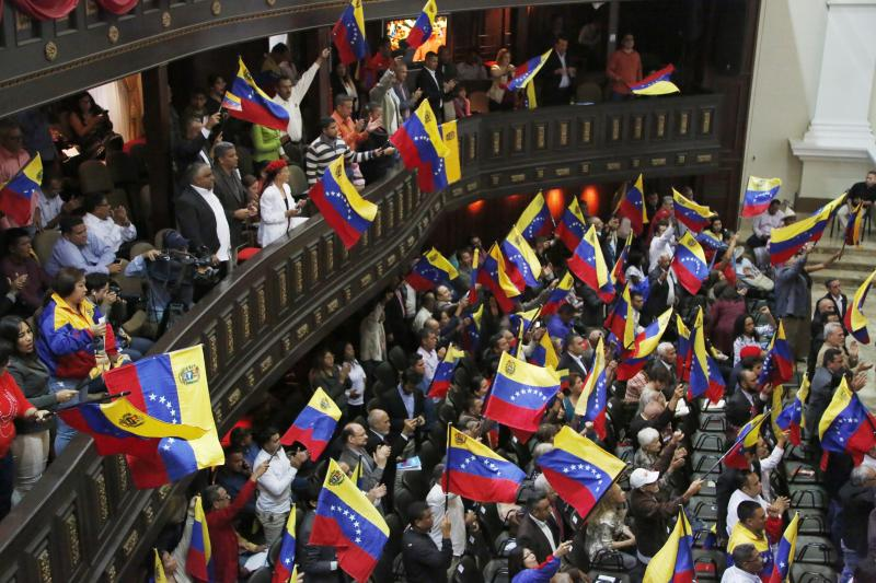 Members of the National Constituent Assembly wave Venezuelan flags during a session by the legislative body that is stacked with government allies that rivals the opposition-controlled National Assembly in Caracas, Venezuela, Monday, Aug. 12, 2019. Legislators loyal to Venezuelan President Nicolás Maduro on Monday stripped immunity from four opposition lawmakers accused of treason amid a struggle for control of the crisis-stricken nation, bringing to 18 the number of opposition politicians Maduro's government has threatened with criminal prosecution this year. (AP Photo/Leonardo Fernandez)