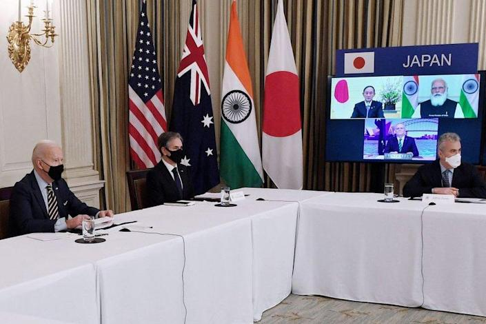 """US President Joe Biden (L), with Secretary of State Antony Blinken (2nd L), meets virtually with members of the """"Quad"""" alliance of Australia, India, Japan and the US, in the State Dining Room of the White House in Washington, DC, on March 12, 2021."""