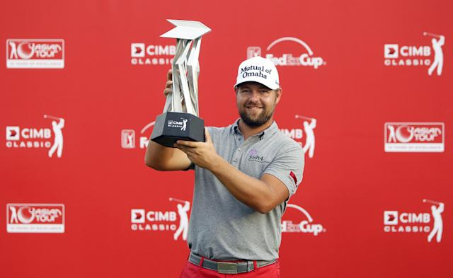 Ryan Moore of the U.S. poses for photographers with his trophy after winning in a playoff of the CIMB Classic golf tournament at the Kuala Lumpur Golf and Country Club in Kuala Lumpur, Malaysia, Monday, Oct. 28, 2013. (AP Photo/Lai Seng Sin)