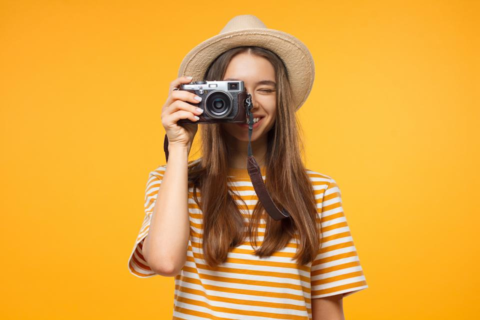 Smiling young girl tourist holding camera, isolated on yellow background