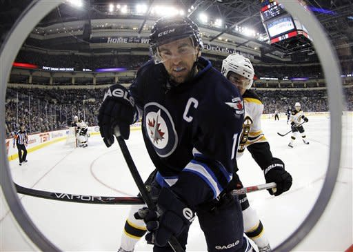 Winnipeg Jets' Andrew Ladd (16) is driven into the boards by Boston Bruins' John Boychuk (55) during the second period of their NHL hockey game, Sunday, Feb. 17, 2013, in Winnipeg, Manitoba. (AP Photo/The Canadian Press, Trevor Hagan)