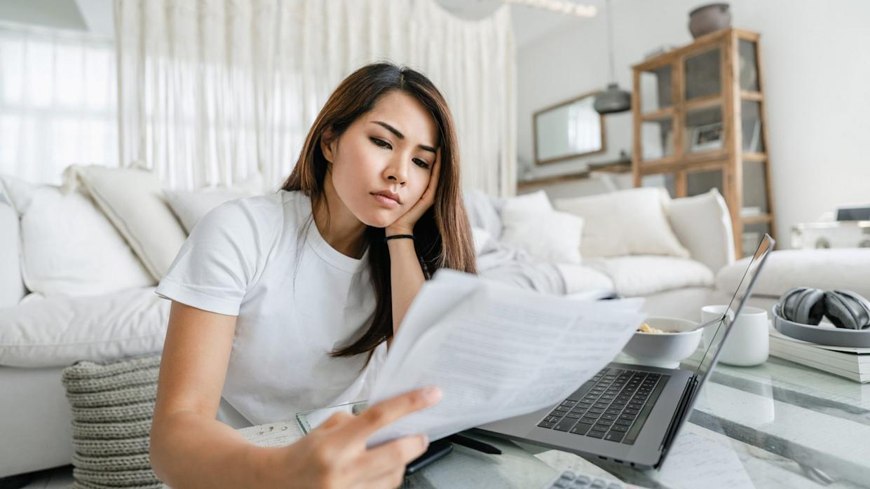 Stressed and worried young Asian woman working from home, handling paperworks and going through her financials.