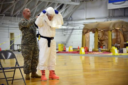 James Knight of U.S. Army Medical Research Institute of Infectious Diseases (USAMRIID) trains U.S. Army soldiers from the 101st Airborne Division (Air Assault), who are earmarked for the fight against Ebola, before their deployment to West Africa, at Fort Campbell, Kentucky October 9, 2014. REUTERS/Harrison McClary
