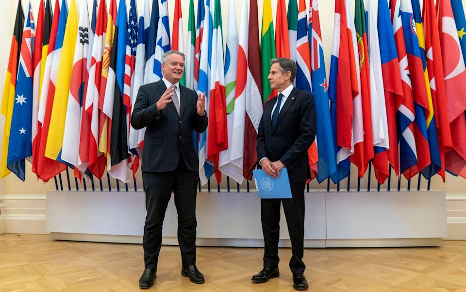 Secretary-General of the Organisation for Economic Cooperation and Development (OECD) Mathias Cormann speaks upon arrival of US Secretary of State Antony Blinken (R) at the OECD headquarters in Paris