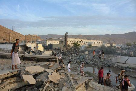 People inspect damage at a site hit by Saudi-led air strikes in the al Qaeda-held port of Mukalla city in southern Yemen