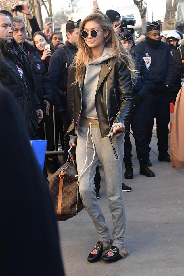<p>Gigi Hadid looked super lax in a gray hoodie and matching sweatpants with a leather jacket. She made the casual outfit a little more fashion-forward with fur-lined Gucci slides. <em>(Photo: Getty Images)</em> </p>