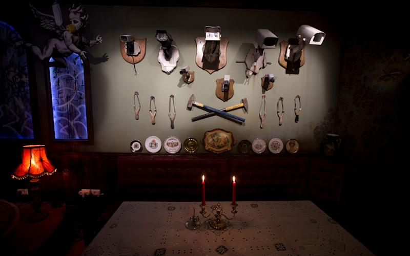 A wall decorated with security cameras and slingshots is seen in the bar area - Credit: Dusan Vranic/AP