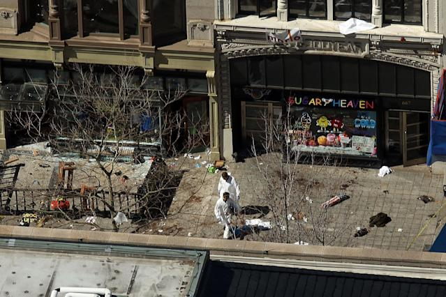 BOSTON, MA - APRIL 17: Investigators stand at the scene of twin bombings at the Boston Marathon on April 17, 2013 in Boston, Massachusetts. The explosions, which occurred near the finish line of the 116-year-old Boston race on April 15, resulted in the deaths of three people with more than 170 others injured. Security has been heightened across the nation as the search continues for the person or people behind the bombings. (Photo by Spencer Platt/Getty Images)