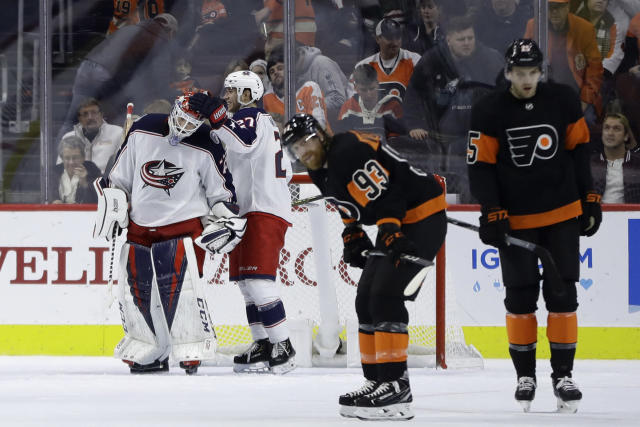 Columbus Blue Jackets' Sergei Bobrovsky, from left, and Ryan Murray (27) celebrate past Philadelphia Flyers' Jakub Voracek (93) and James van Riemsdyk (25) after an NHL hockey game, Saturday, Dec. 22, 2018, in Philadelphia. Columbus won 4-3. (AP Photo/Matt Slocum)