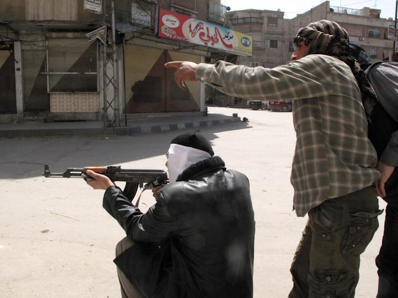 In this Friday, April 6, 2012 photo, Free Syrian Army fighters try to spot a sniper during fighting with Syrian troops in a suburb of Damascus, Syria. Syrian government shelling and offensives against rebel-held towns killed dozens of people across the country on Saturday, activists said, as the U.S. posted online satellite images of troop deployments that cast further doubt on whether the regime intends to comply with an internationally sponsored peace plan. (AP Photo)