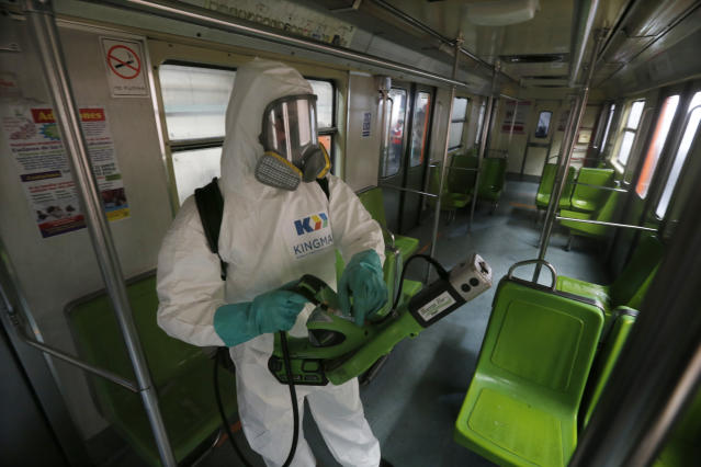 A cleaner wearing protective mask and suit disinfects a metro carriage in Mexico City. (AP)