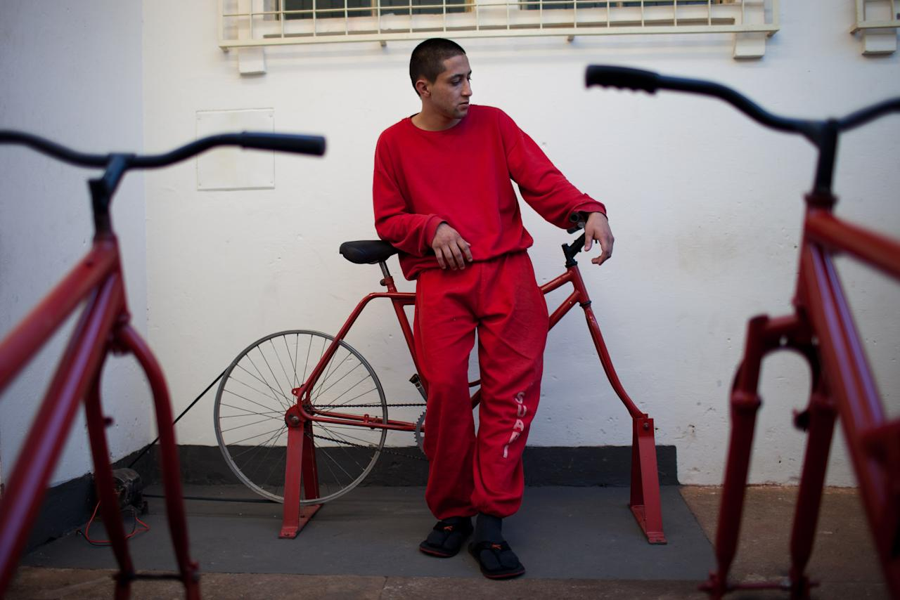 In this photo taken Friday, July 6, 2012, an inmate takes a break from pedaling a stationary bike to charge car batteries at a prison in Santa Rita do Sapucai, Minas Gerais state, Brazil. An innovative program allows inmates at this medium-security prison to shave days off their sentence in exchange for riding stationary bikes hooked up to converted car batteries that are used to illuminate Santa Rita do Sapucai's town square. (AP Photo/Felipe Dana)