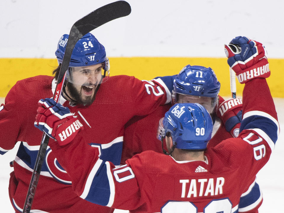 Montreal Canadiens' Brendan Gallagher (11) celebrates with Phillip Danault (24) and Tomas Tatar (90) after scoring against the Winnipeg Jets during the second period of an NHL hockey game Saturday, March 6, 2021, in Montreal. (Graham Hughes/The Canadian Press vIa AP)