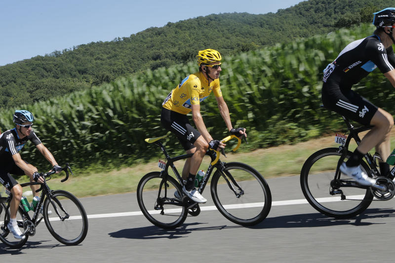 Bradley Wiggins of Britain, wearing the overall leader's yellow jersey, rides with teammates Christian Knees of Germany, right, and Michael Rogers of Australia, left, during the 15th stage of the Tour de France cycling race over 158.5 kilometers (98.5 miles) with start in Samatan and finish in Pau, France, Monday July 16, 2012. (AP Photo/Laurent Cipriani)