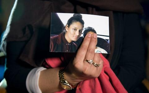 Renu, eldest sister of Shamima Begum, 15, holds her sister's photo while being interviewed by the media at New Scotland Yard, central London - Credit: PA