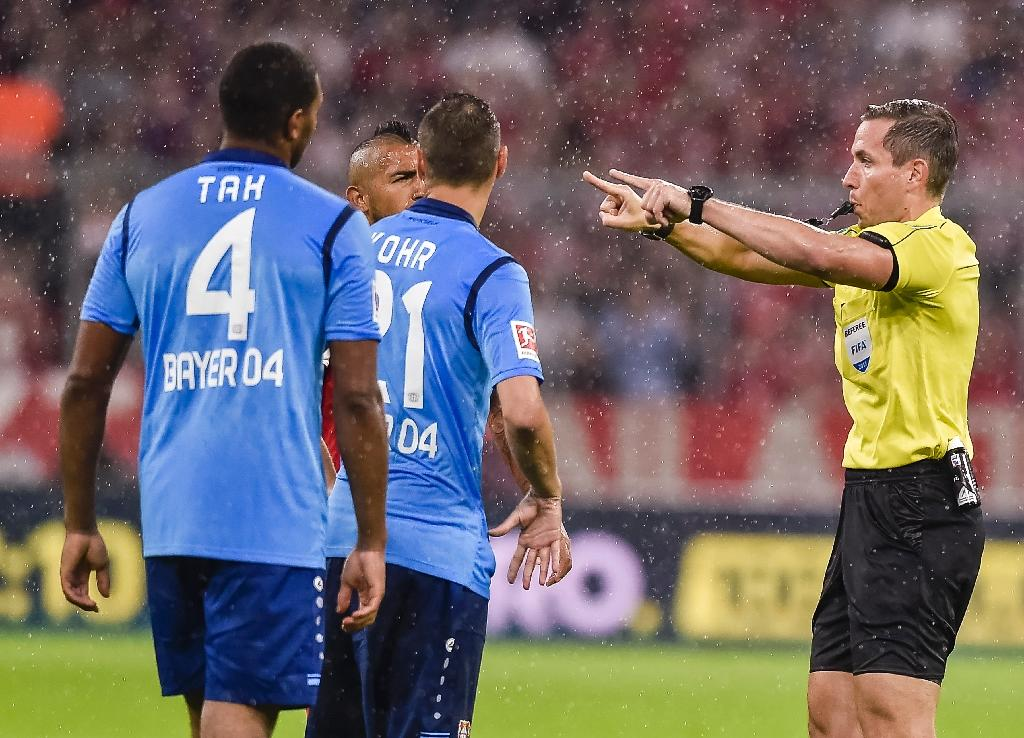German referee Tobias Stieler gestures for the video assistant referee to review a decision during the Bundesliga match between Bayern Munich and Bayern Leverkusen on August 18, 2017 (AFP Photo/Guenter SCHIFFMANN)