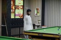 Mohammad Ikram observes during playing snooker at a local snooker club in Samundri town, Pakistan, Sunday, Oct. 25, 2020. Ikram, 32, was born without arms, but everyone simply admires his snooker skills when he hits the cue ball with his chin and pots a colored ball on a snooker table. He lives in a remote rural town of Punjab province and his physical disability doesn't come in his way to fulfill his childhood dream of playing the game of snooker. (AP Photo/Anjum Naveed)