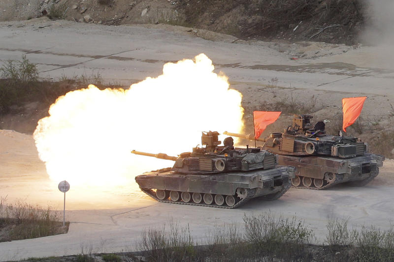 FILE - In this April 26, 2017, file photo, U.S. Army's M1 A2 tanks fire during South Korea-U.S. joint military live-fire drills at Seungjin Fire Training Field in Pocheon, South Korea, near the border with North Korea. The South Korean and U.S. militaries have postponed on Thursday, Feb. 27, 2020, their annual joint drills out of concerns over a virus outbreak. (AP Photo/Ahn Young-joon, File)