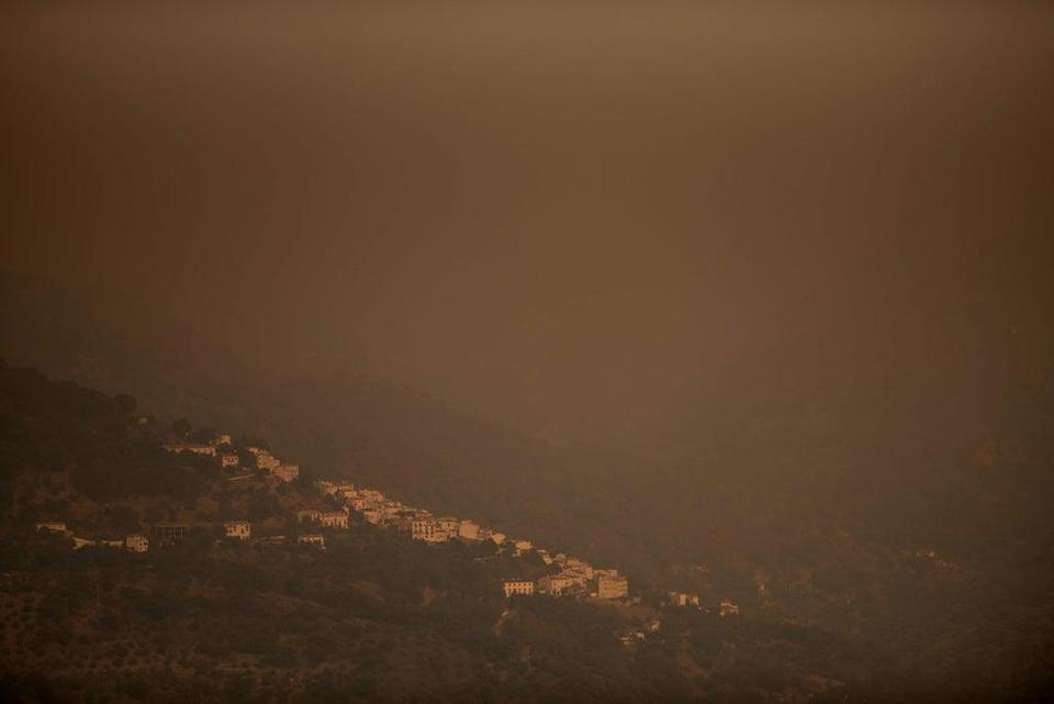The evacuated village of Jubrique, shrouded in smoke, is shown from Algatocin (AFP via Getty Images)