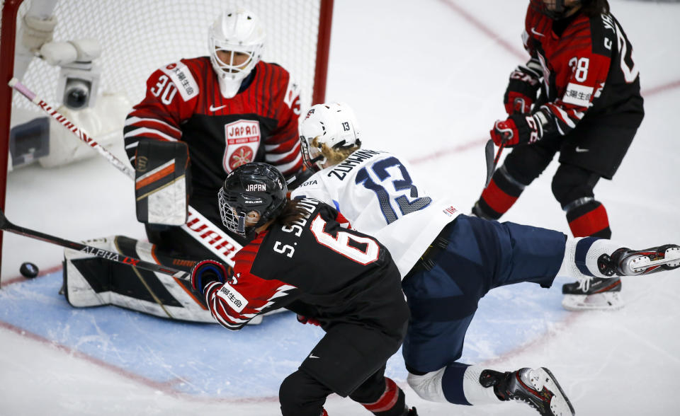 Grace Zumwinkle (13), of the United States, scores against Japan goalie Akane Konishi, left, as she is checked by Japan's Sena Suzuki during third-period quarterfinal IIHF women's world championship hockey game action in Calgary, Alberta, Saturday, Aug. 28, 2021. (Jeff McIntosh/The Canadian Press via AP)