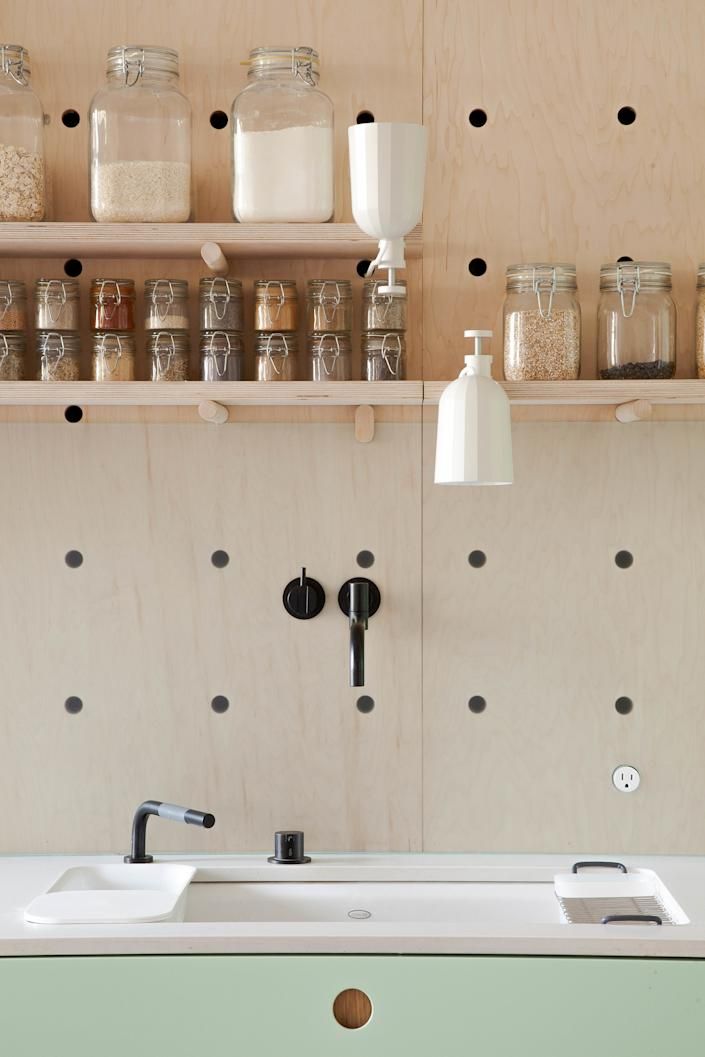 "<div class=""caption""> An oversized pegboard covers the wall behind the sink, with modular shelves for storing dry goods and spices. ""It was custom-designed by us, constructed of maple-faced ApplePly,"" Ruth says. The sink is the <a href=""https://fave.co/3auyJyh"" rel=""nofollow noopener"" target=""_blank"" data-ylk=""slk:Riverby"" class=""link rapid-noclick-resp"">Riverby</a> by Kohler, which comes with an inset colander, tiny cutting board, and utility rack; the wall-mounted faucet and spray are by Vola. </div> <cite class=""credit"">Peter Dressel 2018</cite>"
