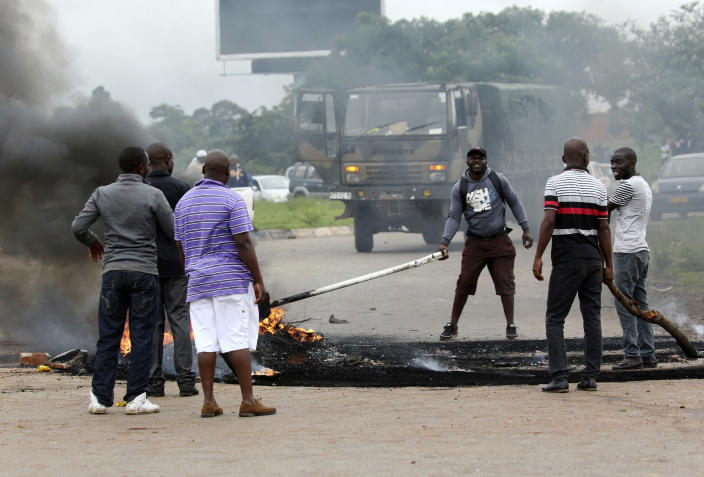 Plain clothed soldiers remove the barricade as protestors gather during a demonstration over the hike in fuel prices in Harare, Zimbabwe, Tuesday, Jan. 15, 2019. A Zimbabwean military helicopter on Tuesday fired tear gas at demonstrators blocking a road and burning tires in the capital on a second day of deadly protests after the government more than doubled the price of fuel in the economically shattered country. (AP Photo/Tsvangirayi Mukwazhi)