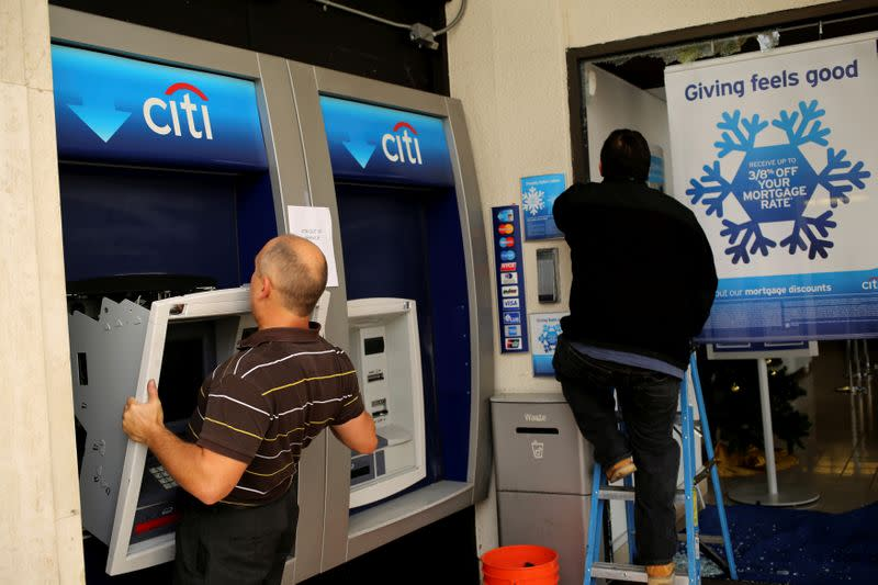 FILE PHOTO: A worker replaces an ATM machine at a bank building on  Shattuck Avenue, in Berkeley
