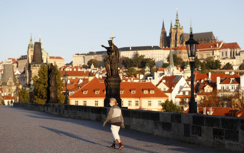 A woman wearing a face mask walks across the medieval Charles Bridge in Prague, Czech Republic, Friday, Sept. 18, 2020. The Czech Republic has been been facing the second wave of infections. The number of new confirmed coronavirus infections has been setting new records almost on a daily basis, currently surpassing 3,000 cases in one day for the first time. (AP Photo/Petr David Josek)