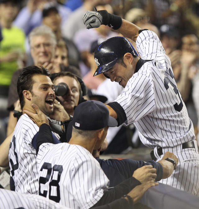 New York Yankees' Ichiro Suzuki, right, celebrates his second home run with Nick Swisher, left, and others as he returns to the dug out during the sixth inning of the baseball game against the Boston Red Sox Sunday, Aug. 19, 2012 at Yankee Stadium in New York. (AP Photo/Seth Wenig)
