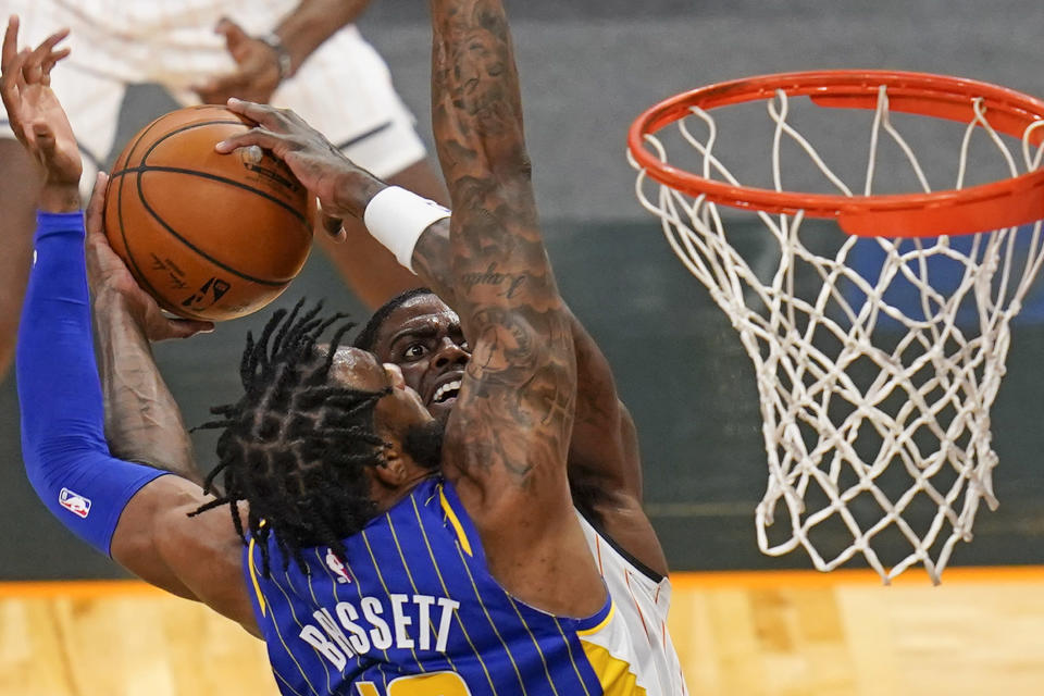 Orlando Magic guard Dwayne Bacon, back right, goes up for a shot against Indiana Pacers forward Oshae Brissett during the second half of an NBA basketball game, Sunday, April 25, 2021, in Orlando, Fla. (AP Photo/John Raoux)